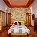 Основната спалня с облицовка на една от стените с камък
