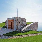 Озеленият покрив на къщата, засаден с местни устойчиви тревни видове, я слива с околността