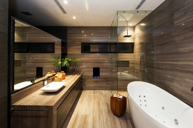 Банята е с голяма вана и облицовки на стените с дърво
