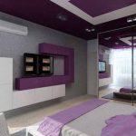 Етажерки с геометрична форма с място за телевизор са поставени на стената срещу леглото