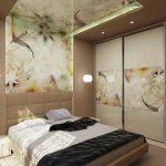 На стената зад леглото е поставено огледало с принт с флорални мотиви, който продължава и по тавана на помещението