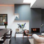 Окачен таван и LED осветление в дневната зона, обзаведена с камина и бели мебели