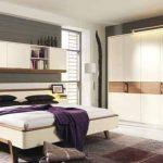 Сиво и лилаво като акценти в спалнята, обзаведена с бели мебели