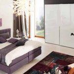 Бели стени, бял гардероб, светъл под и... легло с лилава облицовка