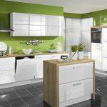 Бяла кухня с акценти от дърво и зелени стени на помещението