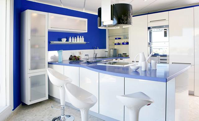 Бяла кухня със син плот и сини стени на помещението