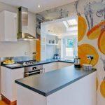 Бяла кухня със стоманеносин плот и оранжеви акценти на стените